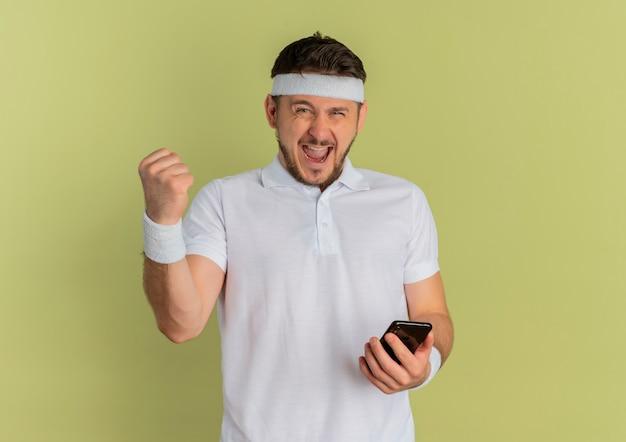 Giovane uomo di forma fisica in camicia bianca con la fascia che tiene smartphone alzando il pugno in piedi felice ed eccitato su sfondo verde oliva