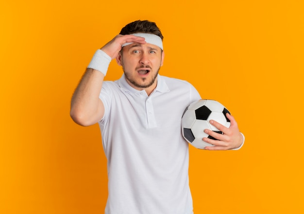 Giovane uomo fitness in camicia bianca con fascia tenendo il pallone da calcio guardando la telecamera confusa in piedi su sfondo arancione
