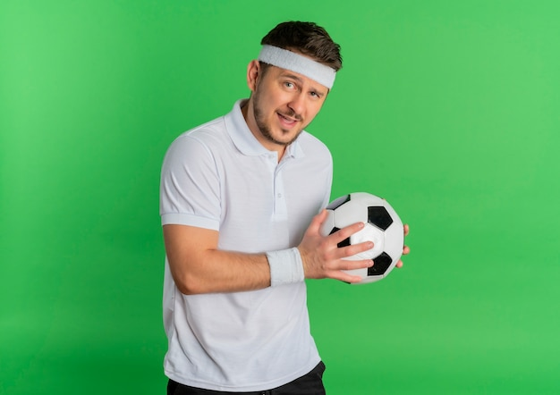 Giovane uomo fitness in camicia bianca con fascia tenendo il pallone da calcio guardando la telecamera sorridendo allegramente in piedi su sfondo verde