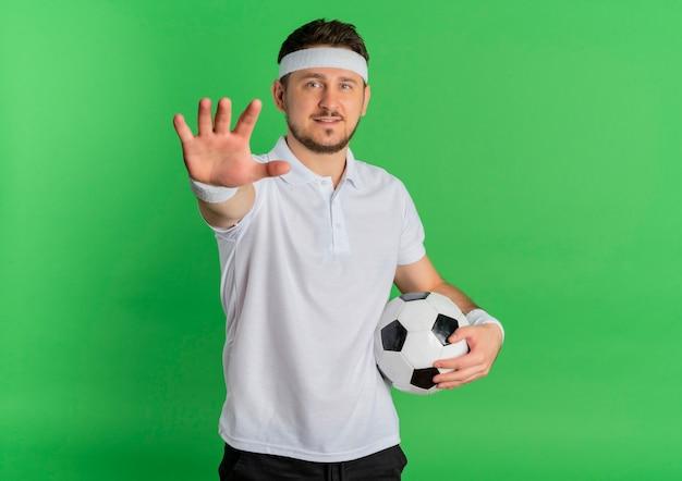 Giovane uomo fitness in camicia bianca con fascia tenendo il pallone da calcio guardando la telecamera con le braccia alzate in piedi su sfondo verde