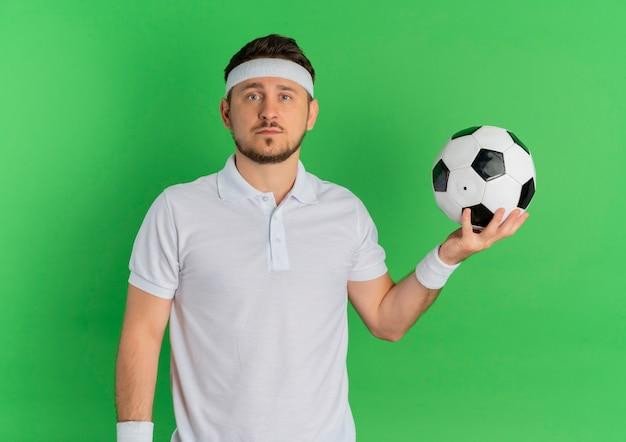 Giovane uomo fitness in camicia bianca con fascia tenendo il pallone da calcio guardando la fotocamera con la faccia seria in piedi su sfondo verde