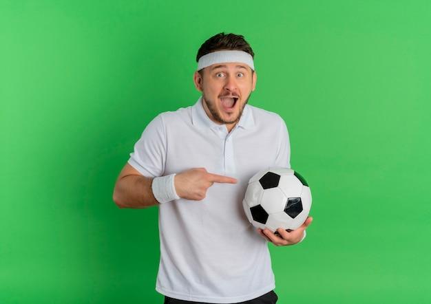 Giovane uomo di forma fisica in camicia bianca con la fascia che tiene il pallone da calcio che indica con il dito indice ad esso felice ed eccitato che sta sopra fondo verde