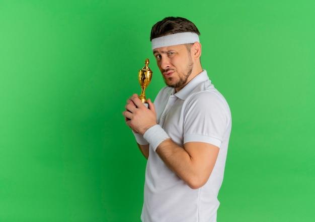 Giovane uomo fitness in camicia bianca con fascia tenendo il trofeo cercando fiducioso in piedi su sfondo verde