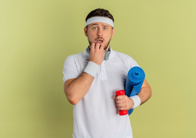 Young fitness man in white shirt with headband holding yoga mat and dumbbell looking at camera surprised standing over olive background
