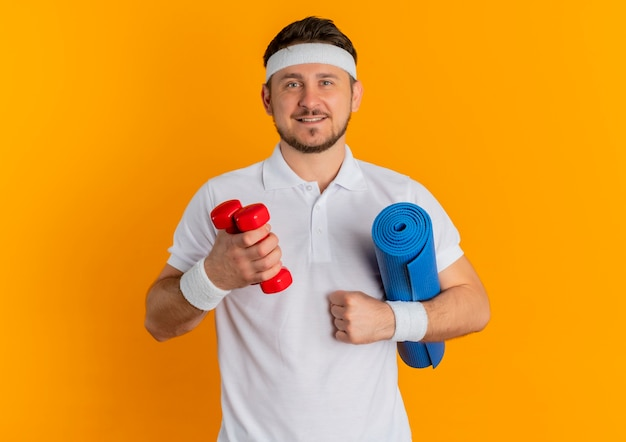 Young fitness man in white shirt with headband holding yoga mat and dumbbells looking confident standing over orange background