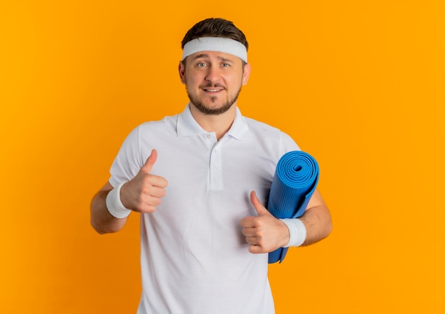 Young fitness man in white shirt with headband holding yoga mat showing thumbs up looking at camera smiling standing over orange background