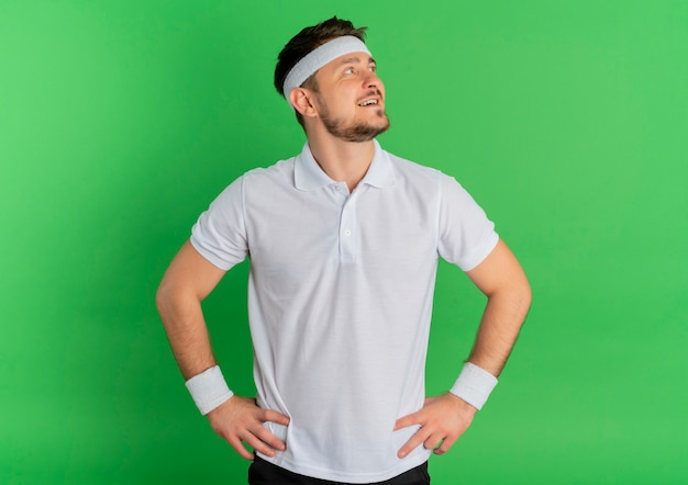 Giovane uomo di forma fisica in camicia bianca con archetto che osserva da parte felice e positivo sorridente fiducioso in piedi su sfondo verde