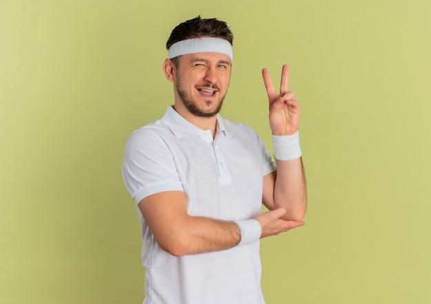 Giovane uomo di forma fisica in camicia bianca con fascia guardando in avanti sorridendo e ammiccando e mostrando il segno di vittoria in piedi sopra il muro di oliva