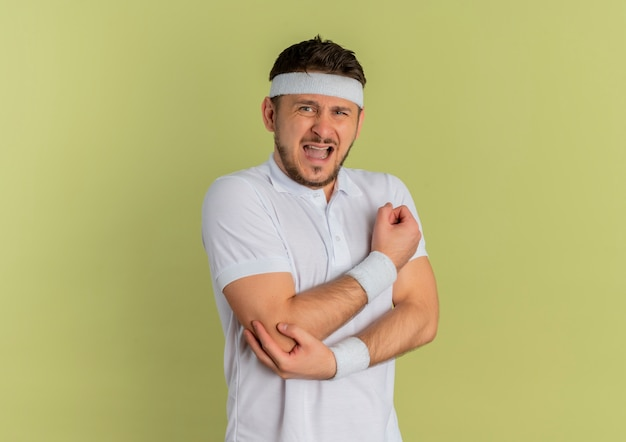 Young fitness man in white shirt with headband looking to the front touching his elbow having pain standing over olive wall