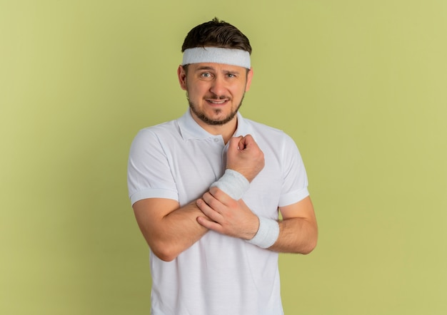 Young fitness man in white shirt with headband looking to the front touching his wrist having pain standing over olive wall