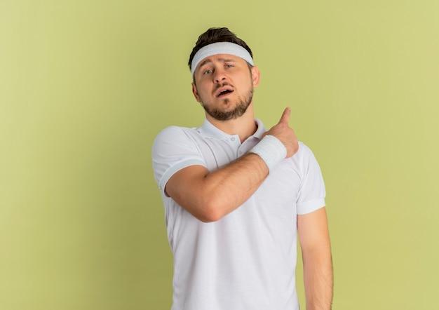 Giovane uomo di forma fisica in camicia bianca con fascia guardando in avanti con espressione fiduciosa, indicando indietro in piedi sopra il muro di oliva