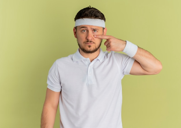 Young fitness man in white shirt with headband pointing with finger to his eye standing over olive wall