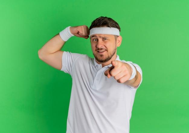 Giovane uomo fitness in camicia bianca con archetto alzando il pugno che mostra i bicipiti, indicando con il dito verso la parte anteriore, in piedi sopra il muro verde