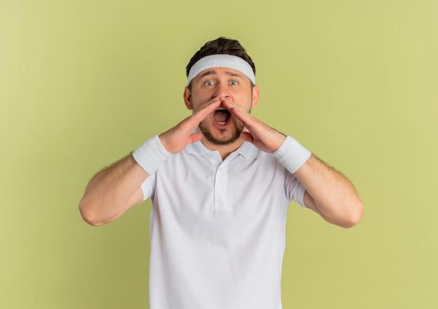 Giovane uomo di forma fisica in camicia bianca con fascia che grida in preda al panico con le mani vicino alla bocca in piedi sopra il muro di oliva
