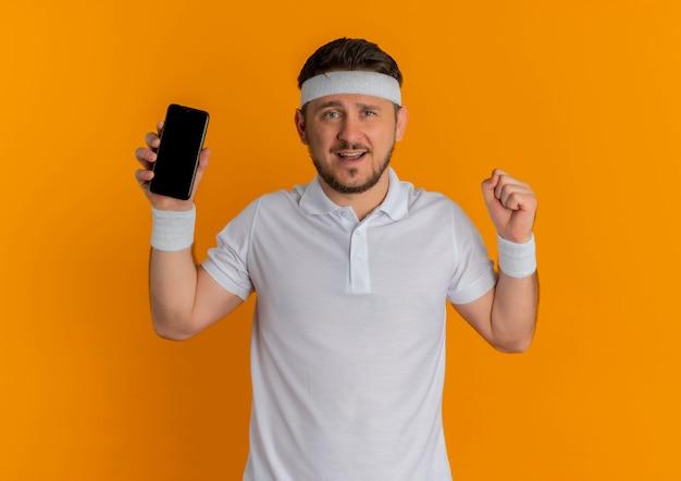 Giovane uomo di forma fisica in camicia bianca con la fascia che mostra il pugno di serraggio dello smartphone felice e positivo in piedi sopra la parete arancione