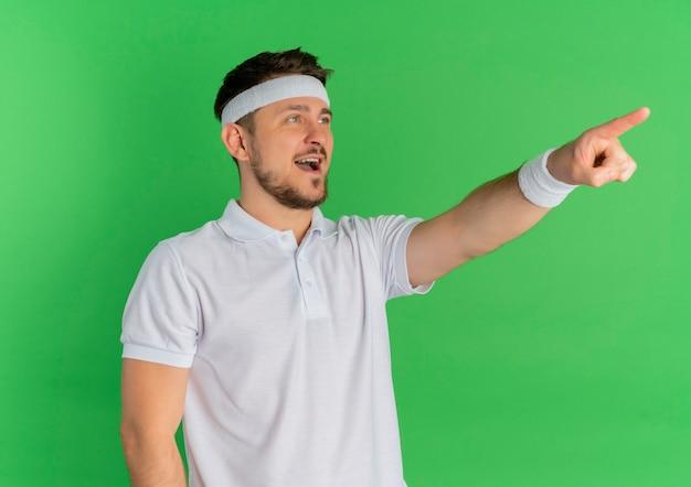 Giovane uomo di forma fisica in camicia bianca con fascia sorridendo allegramente puntando il dito a qualcosa in piedi sopra la parete verde