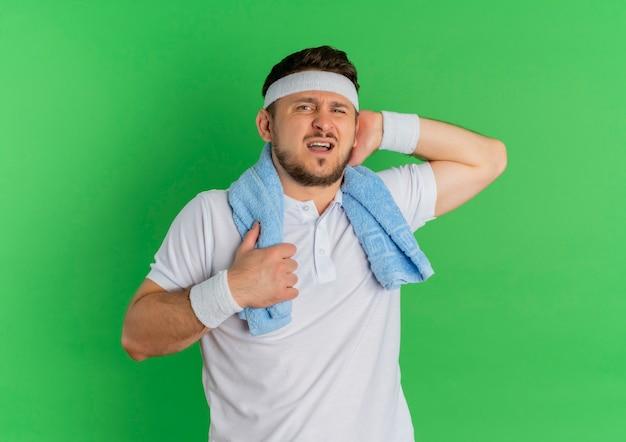 Giovane uomo di forma fisica in camicia bianca con fascia e asciugamano intorno al collo che guarda l'obbiettivo stanco ed esausto dopo l'allenamento in piedi su sfondo verde
