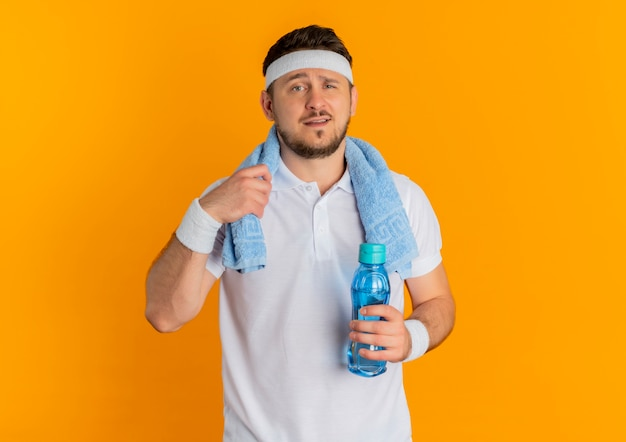 Giovane uomo fitness in camicia bianca con fascia e asciugamano intorno al collo tenendo la bottiglia di acqua che guarda l'obbiettivo con espressione fiduciosa in piedi su sfondo arancione