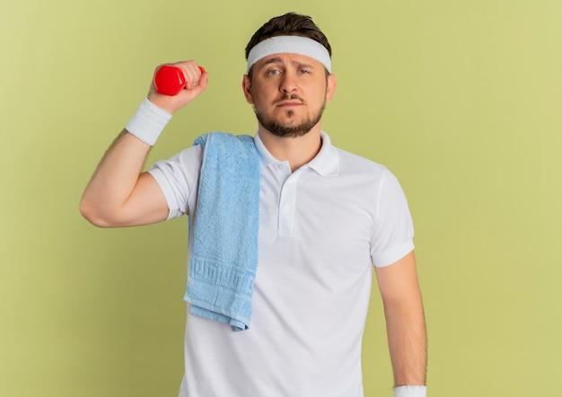 Giovane uomo di forma fisica in camicia bianca con fascia e asciugamano sulla spalla tenendo il manubrio facendo esercizi cercando fiducioso in piedi su sfondo verde oliva
