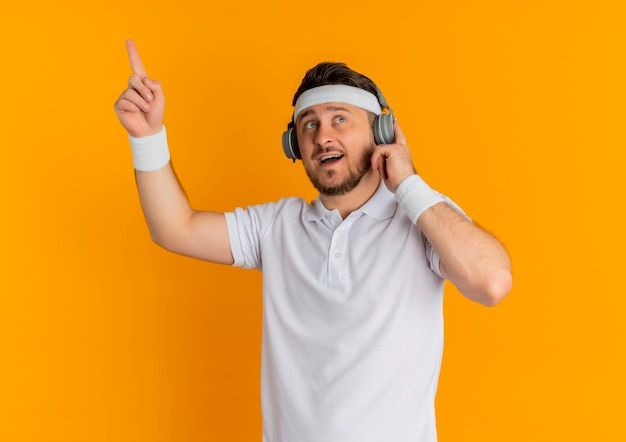 Young fitness man in white shirt with headband with headphones looking surprised and happy showing index finger having great idea standing over orange wall