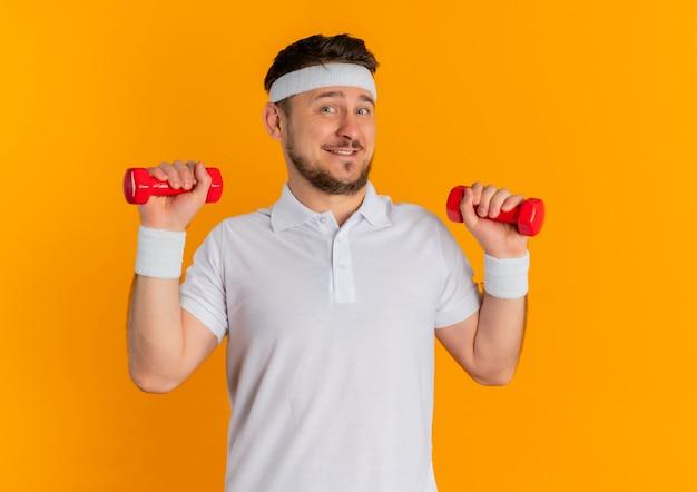Giovane uomo di forma fisica in camicia bianca con la fascia che risolve con i dumbbells che sembrano sorridere fiducioso in piedi sopra la parete arancione