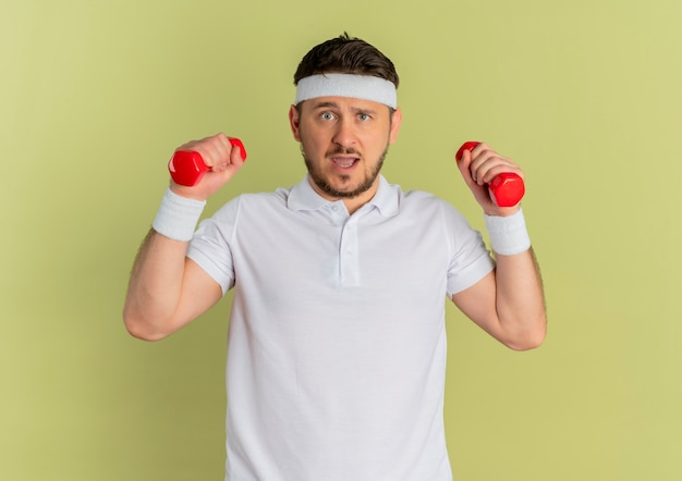 Giovane uomo di forma fisica in camicia bianca con la fascia che risolve con i dumbbells che sembrano confusi in piedi sopra il muro di oliva