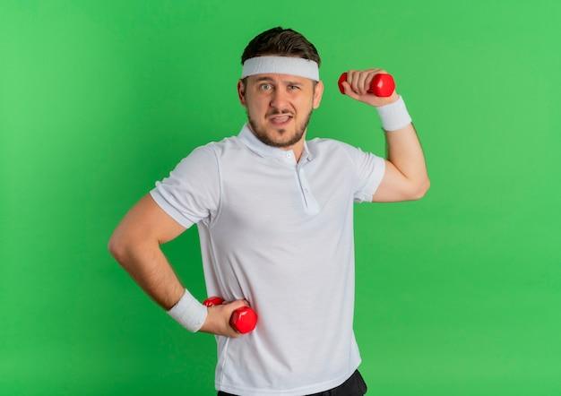 Giovane uomo di forma fisica in camicia bianca con fascia che lavora con manubri teso e fiducioso in piedi sopra la parete verde