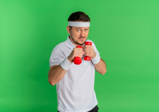Young fitness man in white shirt with headband working out with dumbbells strained standing over green background