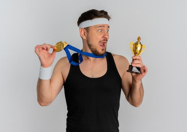 白い背景の上に立って驚いて驚いたように見えるトロフィーを保持している彼の首の周りにヘッドバンドと金メダルを持つ若いフィットネス男