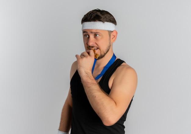 彼の首の周りにヘッドバンドと金メダルを持つ若いフィットネス男は、白い背景の上に立っている彼のメダルを噛んでストレスと緊張