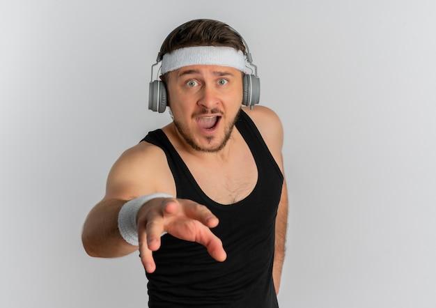 머리띠와 headpones 흰색 배경 위에 서 운동을 할 준비가 자신감 식으로 카메라를 찾고 젊은 피트 니스 남자