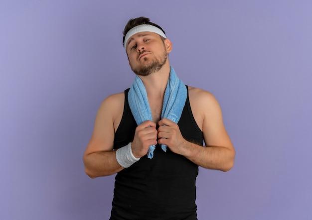 머리띠와 어깨에 수건을 가진 젊은 피트니스 남자는 보라색 벽 위에 자신감이있는 표정으로 자기 만족 서와 함께 앞으로 찾고