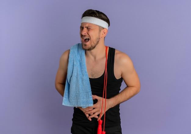 紫色の壁の上に立っている痛みに苦しんで彼の腹に触れて体調不良に見える肩にヘッドバンドとタオルを持つ若いフィットネス男