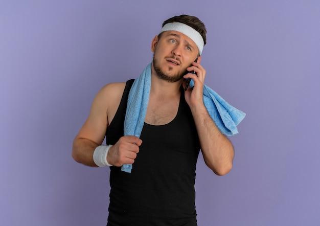 紫色の壁の上に立って混乱しているように見える携帯電話で話している肩にヘッドバンドとタオルを持つ若いフィットネス男