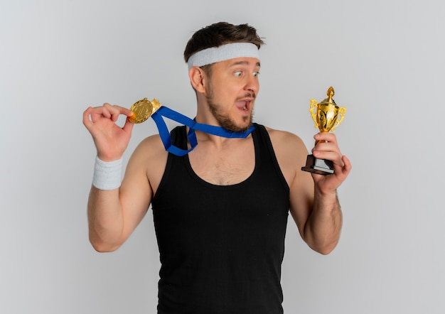 Young fitness man with headband and gold medal around his neck holding trophy looking amazed and surprised standing over white background