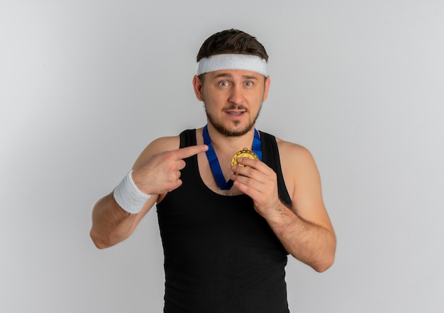Young fitness man with headband and gold medal around his neck pointing with finger to it looking confident standing over white background
