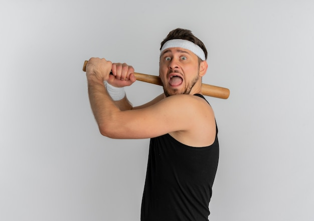 Young fitness man with headband and gold medal swinging a baseball bat scared standing over white background