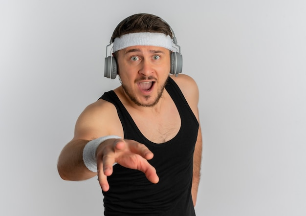 Giovane uomo fitness con archetto e cuffie che guarda l'obbiettivo con espressione fiduciosa pronto a lavorare fuori in piedi su sfondo bianco