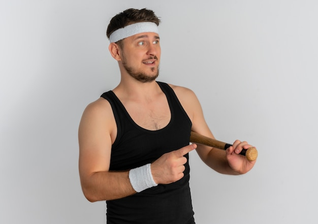 Young fitness man with headband holding baseball bat looking aside confused standing over white background
