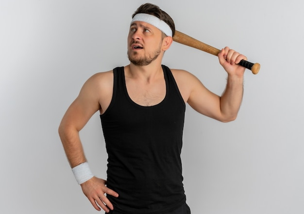 Young fitness man with headband holding baseball bat looking aside with confident expression standing over white background