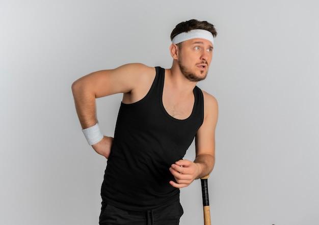 Молодой фитнес-мужчина с повязкой на голову, держащий бейсбольную биту, глядя в сторону с растерянным выражением лица, стоя на белом фоне
