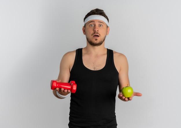 緑のリンゴとダンベルを保持しているヘッドバンドを持つ若いフィットネス男が白い背景の上に立って混乱しているカメラを見て