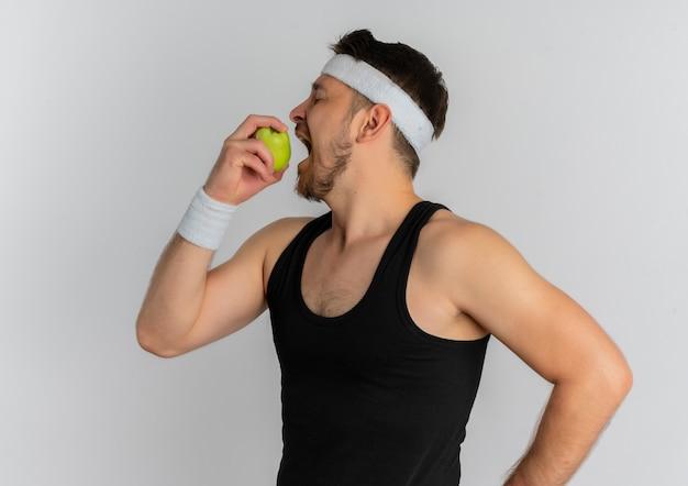 白い背景の上に立ってそれを噛んで青リンゴを保持しているヘッドバンドを持つ若いフィットネス男