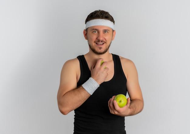 白い背景の上に立っている顔に笑顔でカメラを見て青リンゴを保持しているヘッドバンドを持つ若いフィットネス男