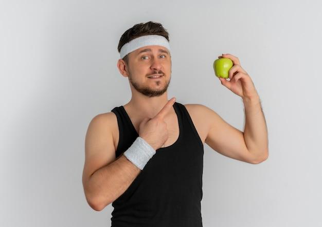 白い背景の上に元気に立って笑ってそれに指で指している青リンゴを保持しているヘッドバンドを持つ若いフィットネス男