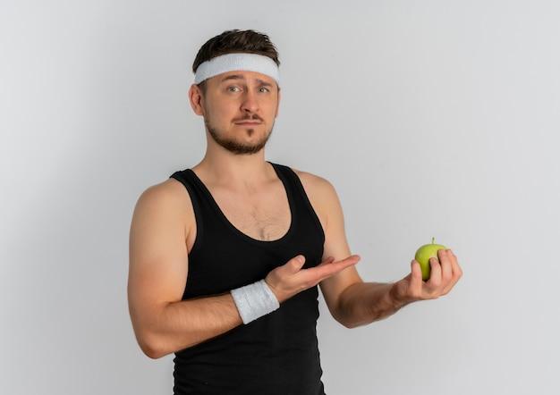 흰색 배경 위에 서 심각한 얼굴로 찾고 팔 오 손으로 제시 녹색 사과 들고 머리띠와 젊은 피트 니스 남자