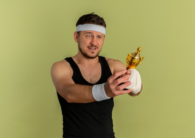 Young fitness man with headband holding his trophy looking at it excited and happy standing over olive background