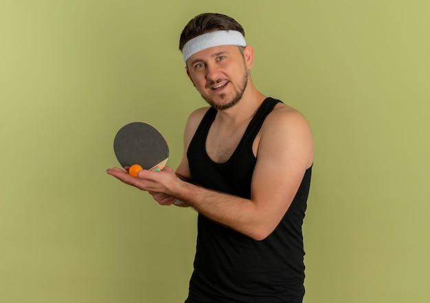 Молодой фитнес-мужчина с повязкой на голову, держащей ракетку и мячи для настольного тенниса, собирается играть, улыбаясь, стоя на оливковом фоне