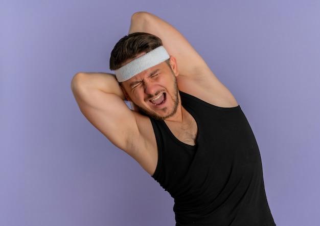 紫色の壁の上に立って自分自身を伸ばす痛みに苦しんでいるヘッドバンドを持つ若いフィットネス男
