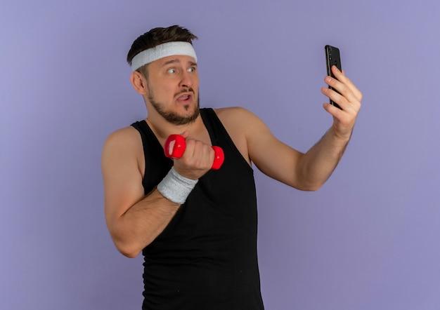 보라색 벽 위에 서있는 혼란 스 러 워 찾고 손에 아령으로 포즈를 취하는 그의 스마트 폰을 사용하여 셀카를 복용하는 머리띠와 젊은 피트 니스 남자